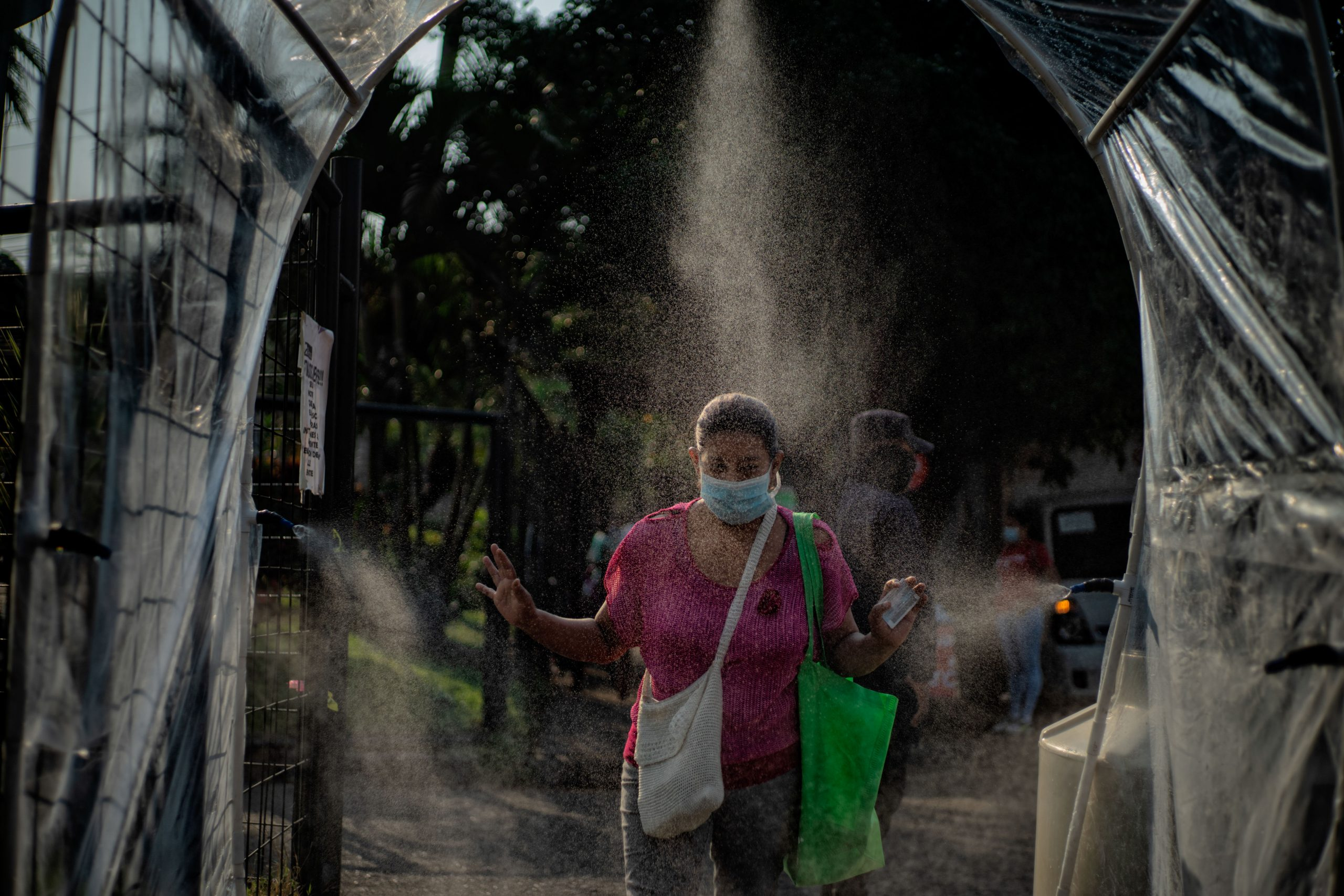 Customers walk through a sanitation tunnel