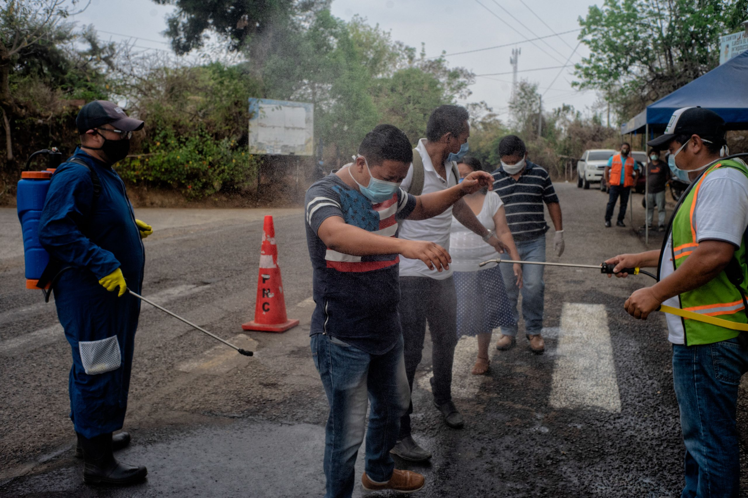People being sprayed with disinfecting solution