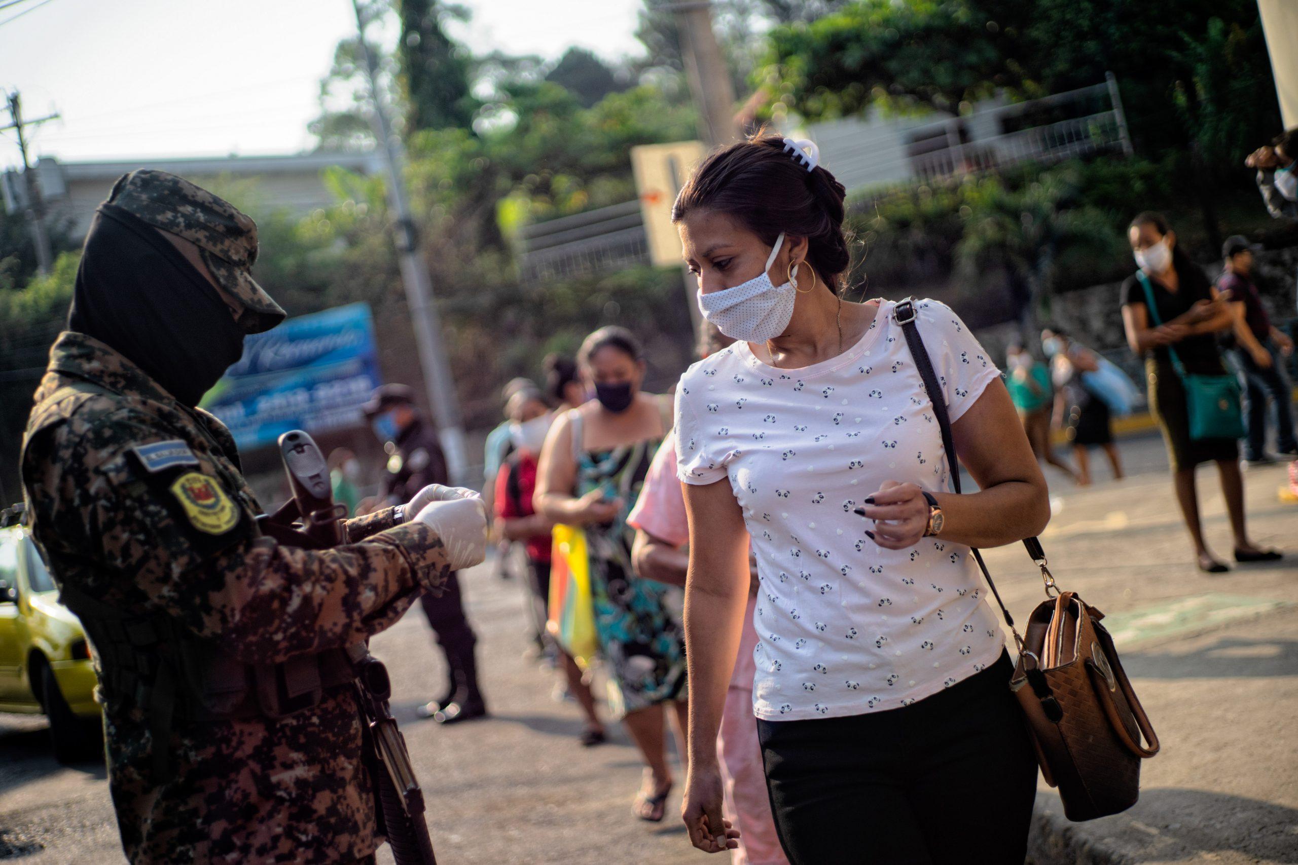 Soldier checks a woman's ID card