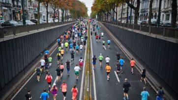 People running on the road. (Martin Zemlickis/Unsplash)