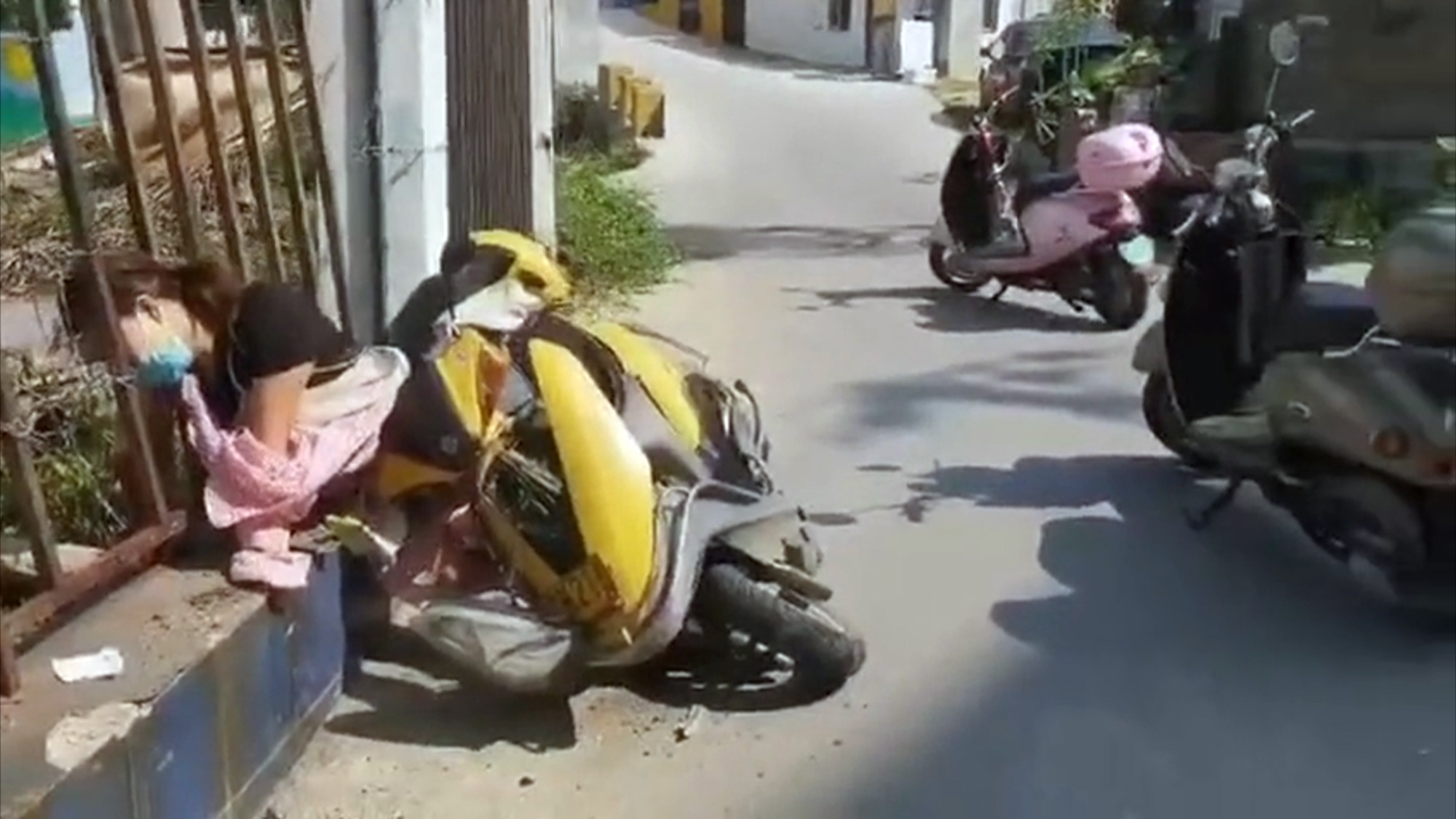 Chinese woman falls off scooter, gets head stuck in fence