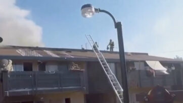 Firefighters on the roof of the building battling an apartment fire near Kings Canyon in Fresno, California on May 3, 2021. (@FresnoFireDepartment/Real Press)
