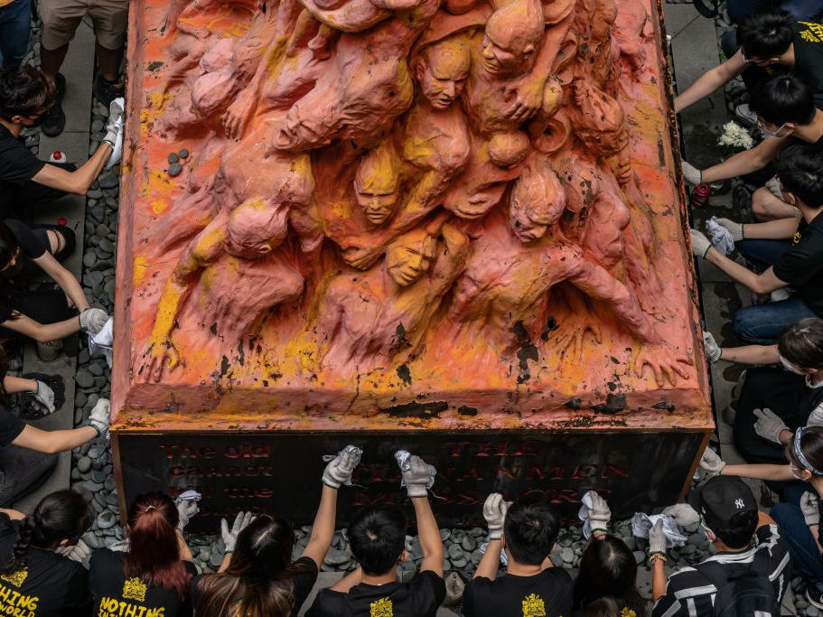 University students clean the Pillar of Shame sculpture by Danish artist Jens Galschiot, to remember the victims of the Tiananmen crackdown in Beijing, at the University of Hong Kong on June 4, 2021 in Hong Kong, China. Hong Kong activists planned private vigils and religious services to commemorate China's deadly Tiananmen Square crackdown in 1989, as a prominent organizer was arrested and thousands of police were deployed to prevent any mass protests. (Anthony Kwan/Getty Images)