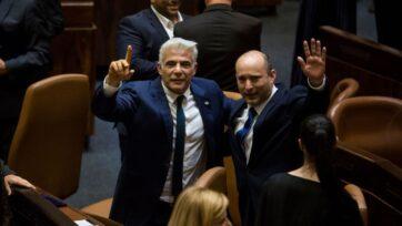 Nuevo primer ministro israelí Naftali Bennett, derecha, y ministro del exterior Yair Lapid, izquierda, celebran tras la aprobación del Knéset de su nuevo gobierno el 13 de junio en Jerusalén. El nuevo gobierno, una gigantesca coalición con una ligera mayoría, terminó el mandato de 12 años de Benjamín Netanyahu. (Amir Levy/Getty Images)