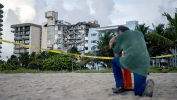 A man prays near where search and rescue operations continue at the site of the partially collapsed 12-story Champlain Towers South condo building on June 25, 2021 in Surfside, Florida. The man, overcome with emotion, said he had lost a relative in the collapse. Over one hundred people are reported as missing as the search-and-rescue effort continues with rescue crews from across Miami-Dade and Broward counties. (Photo by Joe Raedle/Getty Images)