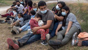 Una familia guatemalteca espera con otros migrantes para abordar un autobús de la Oficina de Aduanas y Protección Fronteriza de Estados Unidos que irá hacia un centro de procesamiento, después de cruzar la frontera de México en La Joya, Texas, el 13 abril. Una oleada de inmigrantes, que incluye un número récord de niños, está haciendo el arduo viaje desde Centroamérica a Estados Unidos, desafiando a las autoridades de migración. (John Moore/Getty Images).