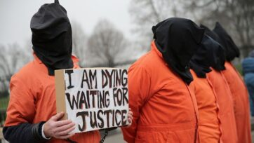 Demonstrators from Witness Against Torture dress in orange jumpsuits and wear black hoods while demanding that then-U.S. President Barack H. Obama close the military prison in Guantanamo, Cuba, outside the White House in January 2016 in Washington, D.C. (Chip Somodevilla/Getty Images)