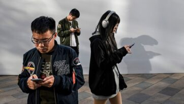 People look a their mobile phones at a luxury mall on October 31, 2019 in Beijing, China. (Kevin Frayer/Getty Images)