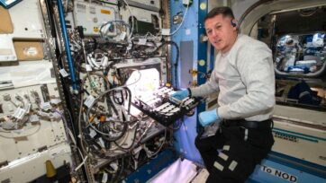 NASA astronaut Shane Kimbrough inserts a science carrier into the Advanced Plant Habitat, which contains 48 Hatch chile pepper seeds NASA started growing on July 12 as part of the Plant Habitat-04 experiment. (NASA/Zenger)