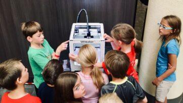 Children gather around a 3D printer. (Adam Winger/Unsplash)