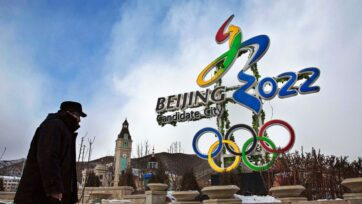 Un hombre chino camina junto a un anuncio de los Juegos Olímpicos de 2022, el 22 de enero de 2016, en el distrito de Chongli, provincia de Hebei, China. (Kevin Frayer/Getty Images)