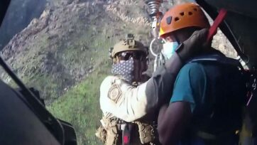 A Guatemalan man and border patrol agents were hoisted into a rescue helicopter in the Baboquivari Mountains southwest of Tucson, Arizona, after the migrant's rescue on Monday. (DVIDS, U.S. Customs and Border Protection Office of Public Affairs/Zenger)