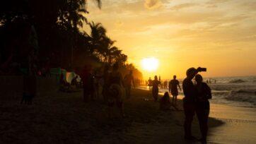 strongTuristas disfrutan de la puesta de sol en un día aglomerado de playa el 20 de julio de 2021. (Mavi Parra/Zenger)/strong