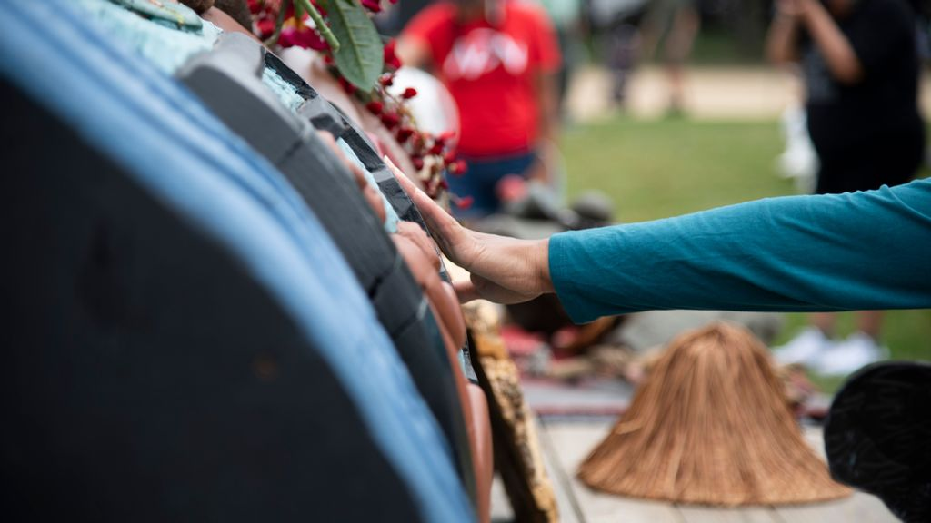 <p>The Lummi Nation transported a 25-foot long totem pole from Washington state to the entrance of the U.S. Capitol.  A woman lays her hand on the totem after a call to pray and empower the 400-year-old cedar. (Zoey Zou/Zenger)</p>