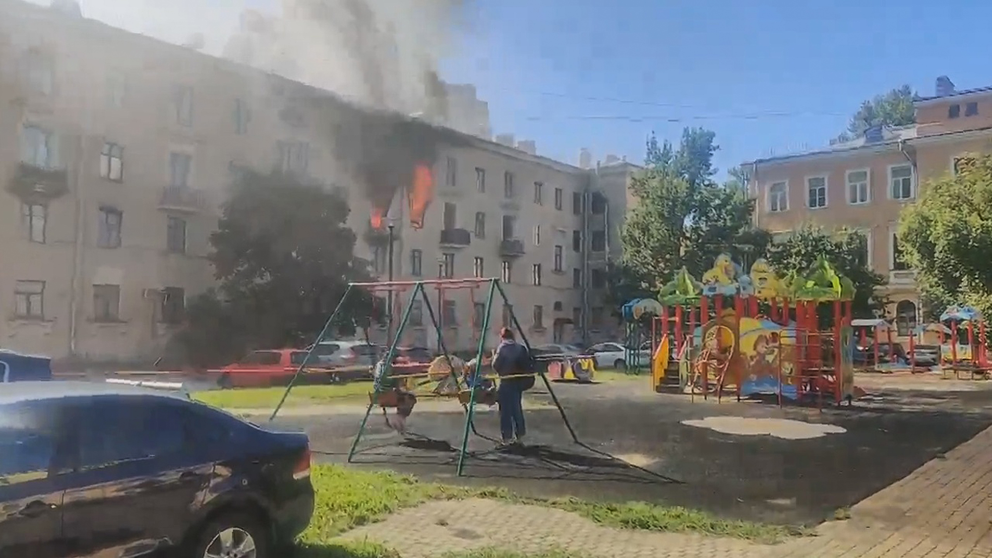 VIDEO: Keeping Their Cool: Boys Play On Swings As Apartment Fire Rages Just Yards Away