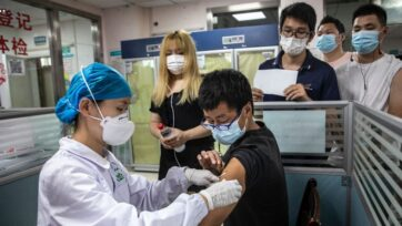 A medical worker administers a dose of COVID-19 vaccine to a resident in Wuhan, China, on June 21. American colleges and universities are weighing whether international students will need to get new jabs if they received vaccines not approved by the U.S. Food and Drug Administration or the World Health Organization. (Getty Images)