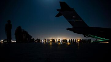 An air crew prepares to load evacuees aboard a C-17 Globemaster III aircraft in support of the Afghanistan evacuation at Hamid Karzai International Airport on August 21, 2021 in Kabul, Afghanistan. (Taylor Crul/U.S. Air Force/Getty Images)