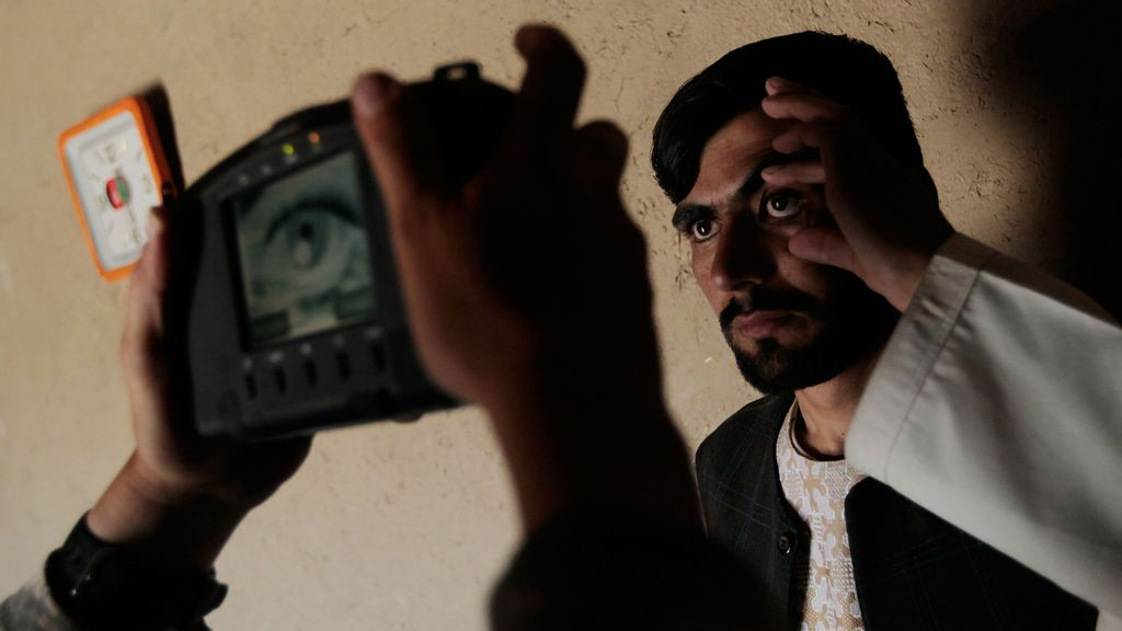 <p>A U.S. Army soldier in the 1-71 Cavalry performs an iris scan for identification purposes with a handheld biometric device June 14, 2010, in rural Dand District, just south of Kandahar, Afghanistan. U.S. soldiers of the 1st Squadron, 71st Cavalry Regiment of the 10th Mountain Division are using biometric tools to catalog all military-aged men and boys in Dand Province, part of a counterinsurgency strategy aimed at finding and identifying Taliban insurgents and legitimizing the government of Afghanistan in the minds of the rural local populace. (Chris Hondros/Getty Images)</p>
