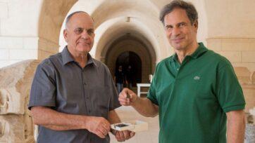 IAA Director Eli Eskosido (left) presents Israeli astronaut Eytan Stibbe with an ancient coin for guardianship while on his trip to space. (Yoli Schwartz/IAA)