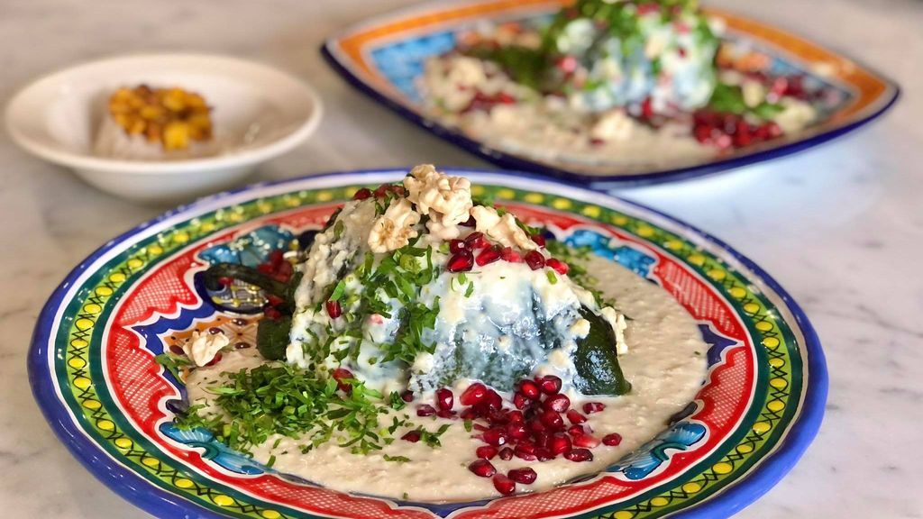 <p>The dish has the colors of the Mexican flag: green, for the peppers and parsley; white for the nogada; and red for the pomegranate seeds sprinkled on top. (Julio Guzmán/Zenger)</p>