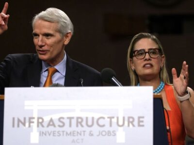 Sen. Rob Portman (R-Ohio) and Sen. Kyrsten Sinema (D-Ariz) answer questions during a news conference following a Senate vote on the bipartisan infrastructure framework on July 28. Democrats are working on a budget reconciliationi /ito pass the bill with a simple majority vote in the Senate. (Alex Wong/Getty Images)