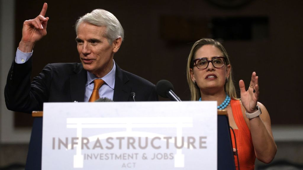 <p>Sen. Rob Portman (R-Ohio) and Sen. Kyrsten Sinema (D-Ariz) answer questions during a news conference following a Senate vote on the bipartisan infrastructure framework on July 28. Democrats are working on a budget reconciliation<i> </i>to pass the bill with a simple majority vote in the Senate. (Alex Wong/Getty Images)</p>