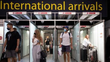 Travelers arrive at Gatwick Airport in London, England, on July 30. Restrictions to and from the UK were put in place as COVID-19 disrupted global travel. (Dan Kitwood/Getty Images)