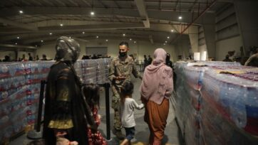 Afghan evacuees being directed into a dining area at Camp As Sayliyah in Doha, Qatar on August 20, 2021. (Jimmie Baker, U.S. Army/Getty Images)