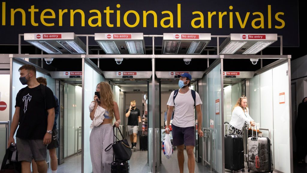 <p>Travelers arrive at Gatwick Airport in London, England, on July 30. Restrictions to and from the UK were put in place as COVID-19 disrupted global travel. (Dan Kitwood/Getty Images)</p>