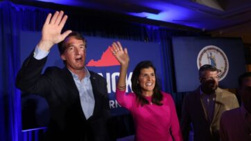 Republican gubernatorial candidate Glenn Youngkin, left, waves to supporters while campaigning with former South Carolina Gov. Nikki Haley in McLean, Virginia, on July 14. Youngkin is running against former Virginia Gov. Terry McAuliffe. (Win McNamee/Getty Images)