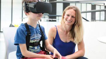 strongJenifer Miehlbradt ayuda a un niño de seis años a probar juegos de realidad virtual para un estudio que descubrió que la coordinación entre la cabeza y el torso se desarrolla más lentamente de lo que se pensaba. (EPFL/Alain Herzog)/strong