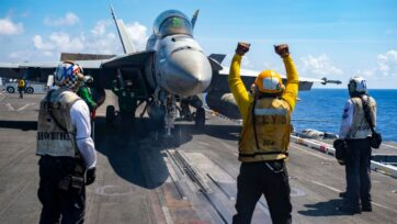 """An F/A-18F Super Hornet, assigned to the """"Bounty Hunters"""" of Strike Fighter Squadron (VFA) 2, prepares to launch from the flight deck of Nimitz-class aircraft carrier USS Carl Vinson (CVN 70), Sept. 29, 2021, in the Philippine Sea. Carl Vinson Carrier Strike Group is on a scheduled deployment in the U.S. 7th Fleet area of operations to enhance interoperability through alliances and partnerships. (U.S. Navy photo by Mass Communication Specialist 3rd Class Isaiah Williams)"""