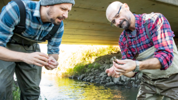 Researchers Eric Larson (left) and Christopher Taylor observe a crayfish. (L. Brian Stauffer)
