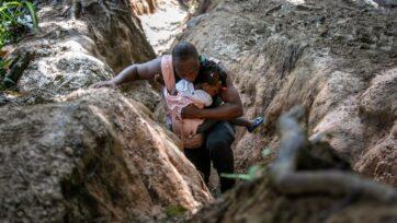 Un padre haitano carga a su hija en el Tapón del Darién, entre Colombia y Panamá, el 5 de octubre. Es el paso más peligroso para los migrantes, en su mayoría haitianos, en el continente. Muchos buscan llegar a Estados Unidos. Otros se quedan en México. (John Moore/Getty Images)