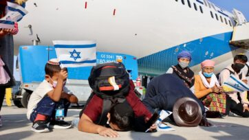 Bnei Menashe immigrants kissing the ground after arriving in Israel on Oct. 13. (Laura Ben David/Shavei Israel)